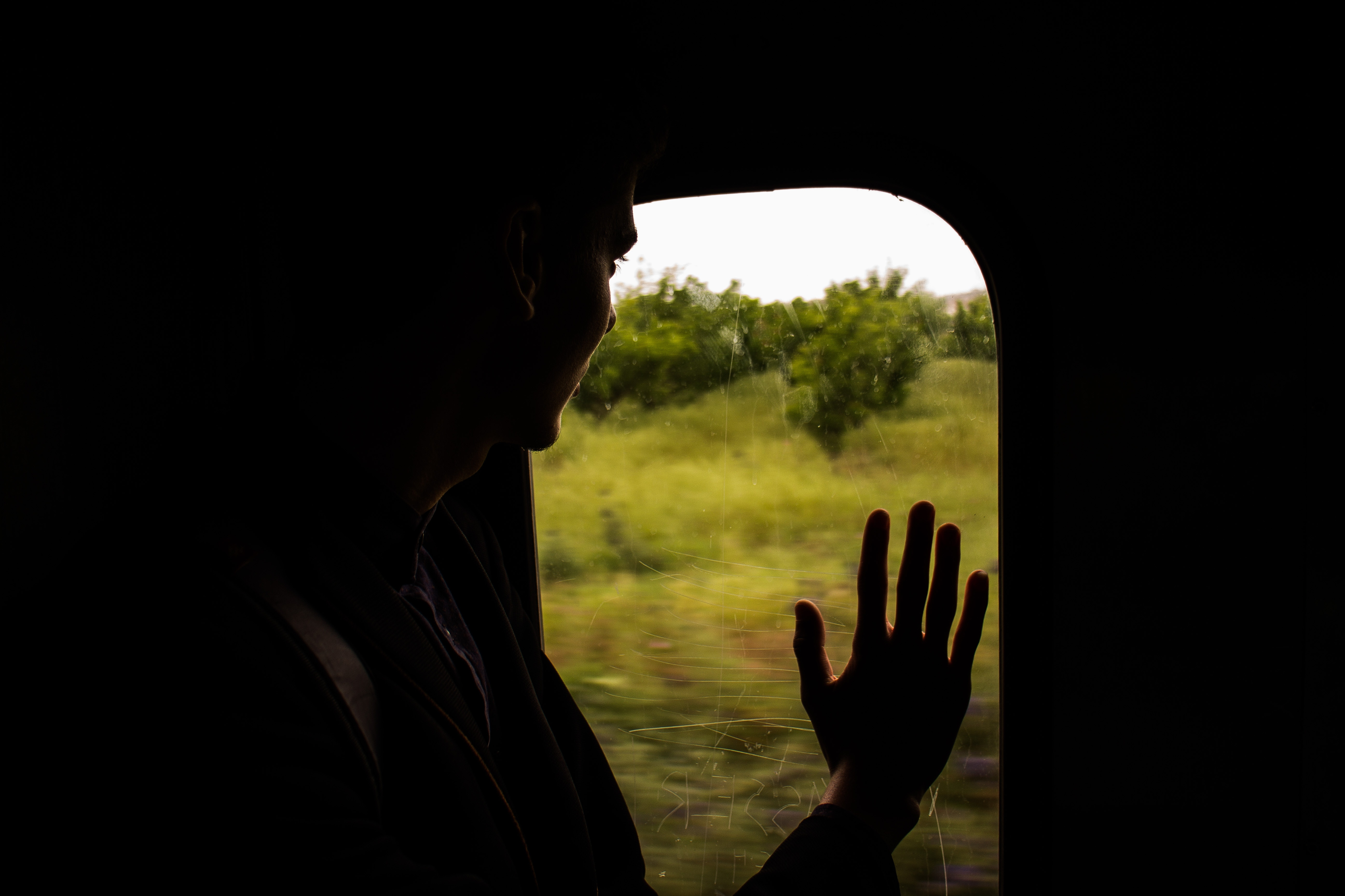 Person looking out of the window of a train.