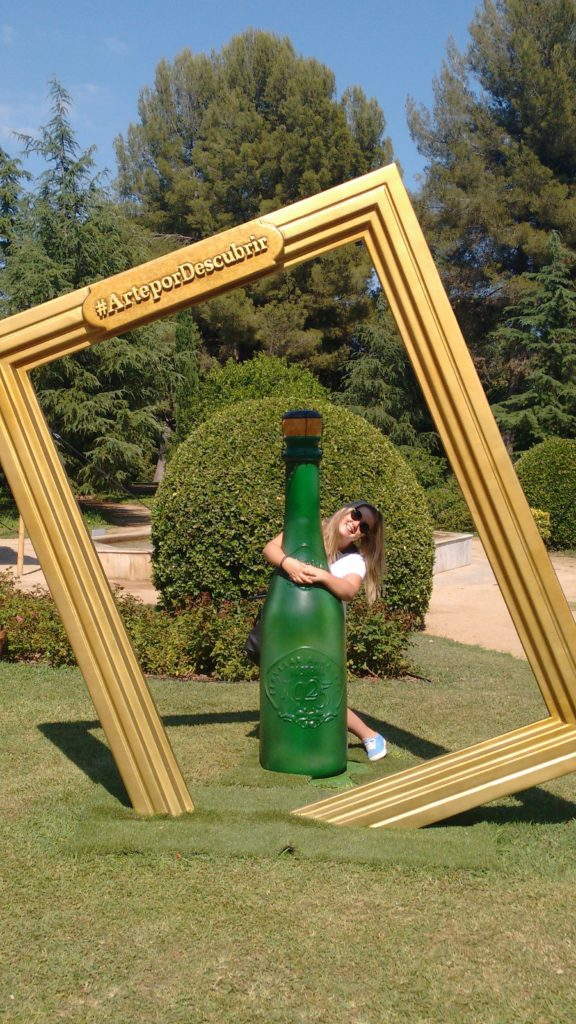 Nikki posing next human sized bottle of champagne