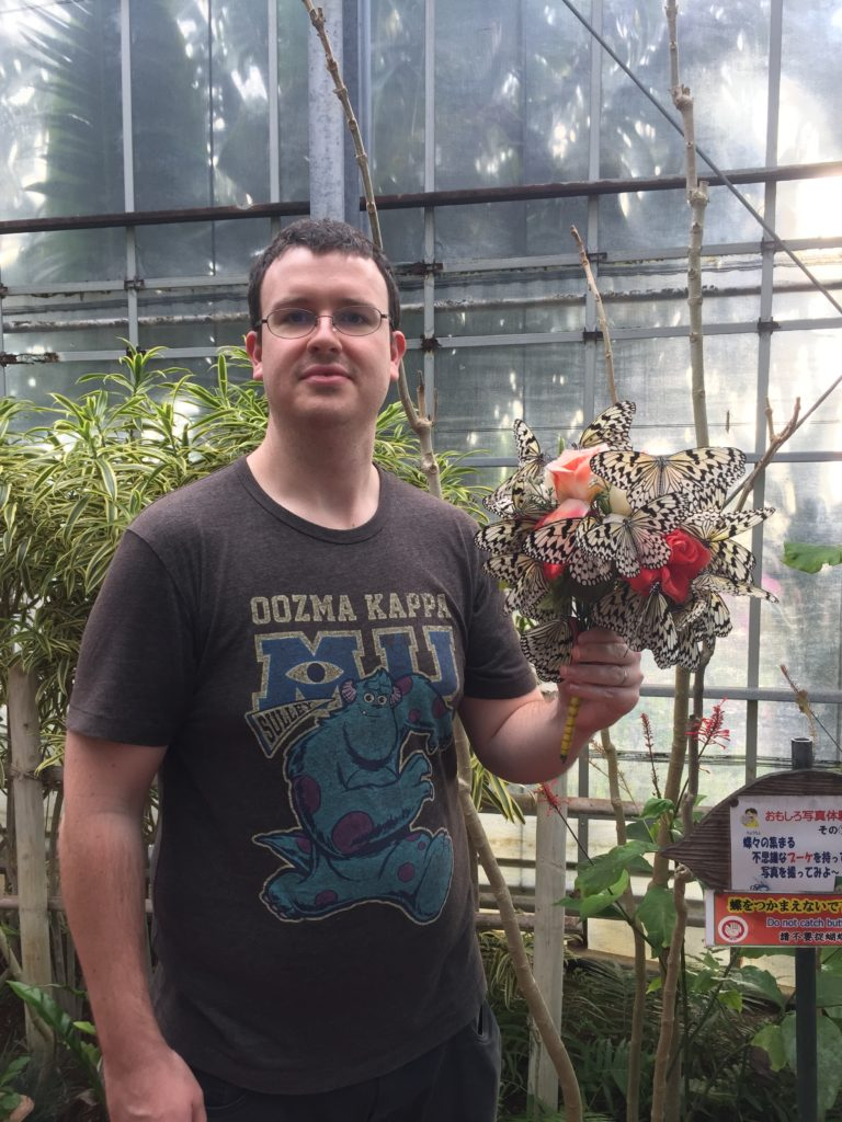 Sheldon holding a bunch of flowers with a butterfly on them