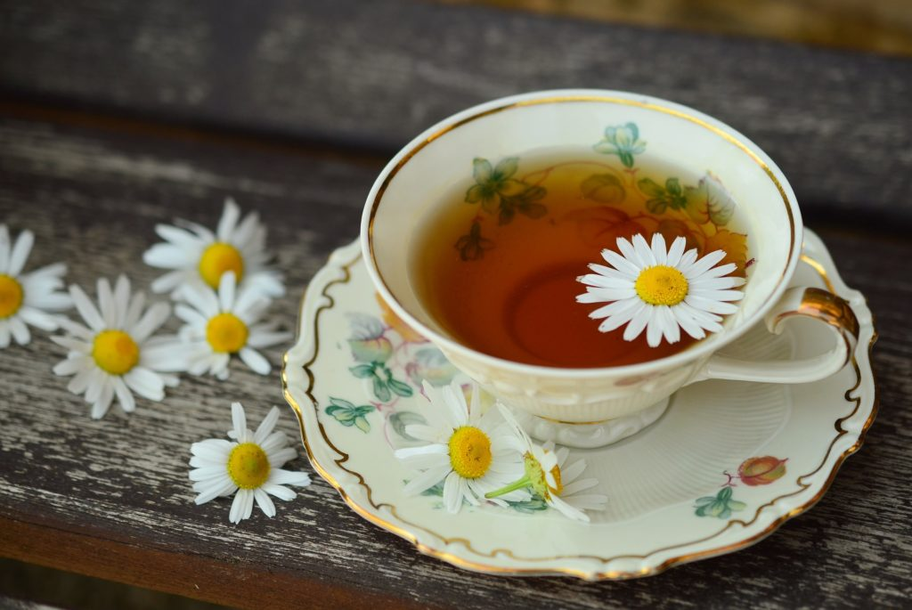 A cup of tea with a flower floating in it
