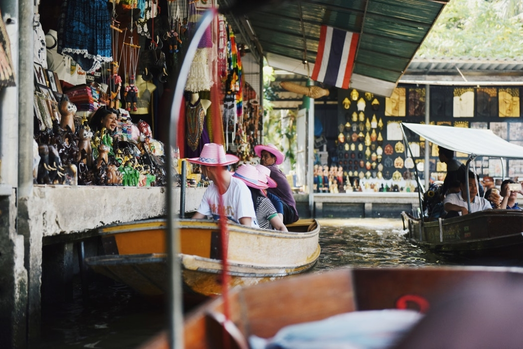 A boat pulling up to a shop in Thailand