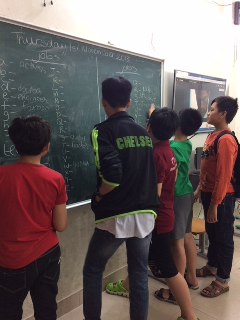 Students writing on a blackboard.