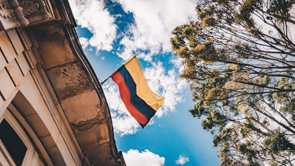 The Colombian flag hanging off the side on a building.