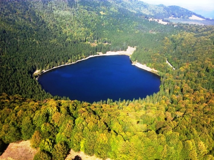 Vulcano lake in Romania surrounded by lush forest.