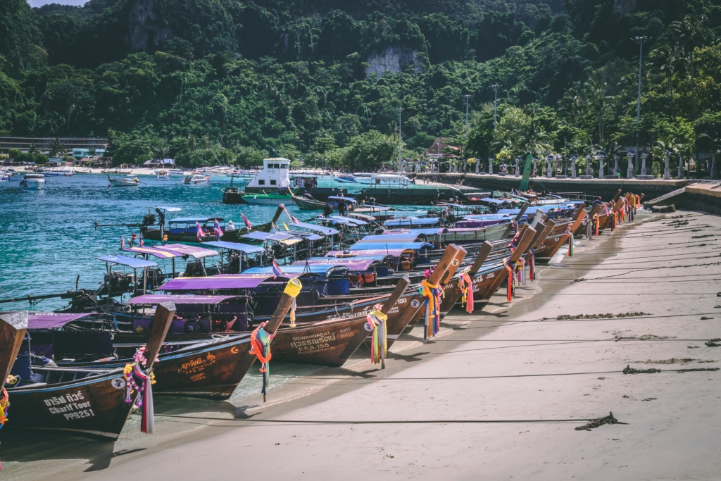 Beautiful beach in Thailand with a load of boats docked up.