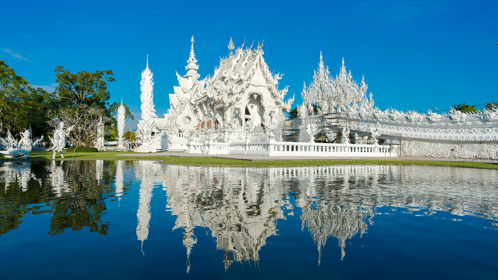 A historical white Thai building overlooking a lake.