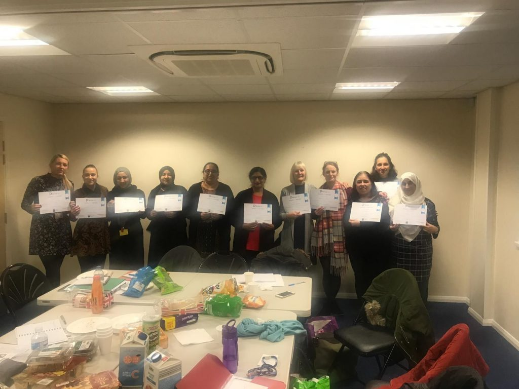 EAL students pose with their certificates upon graduating from the course