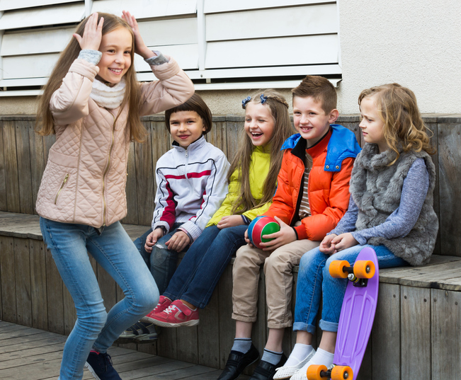 Group of smiling children sitting on bench and playing characters together