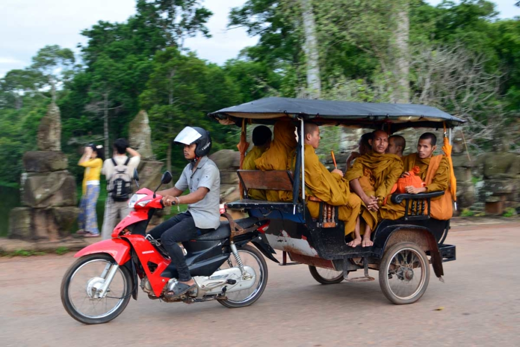 A tuk-tuk filled with monks