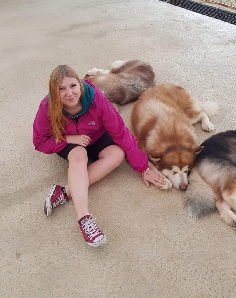 Martha posing with dogs on her TEFL journey